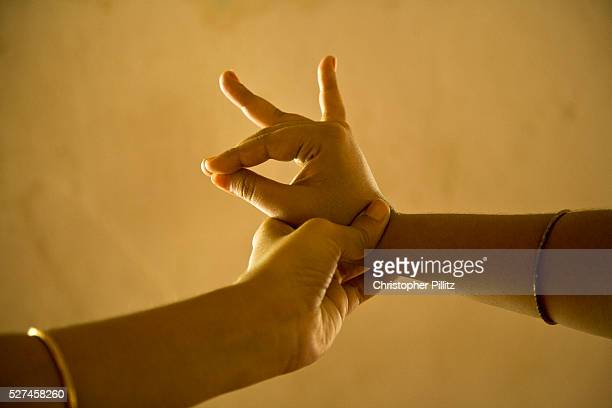 A teacher adjusts a student's hand in the 'mudra' called 'katakamukh' as well as teaching a young dancer movement rhythm and expression known as...