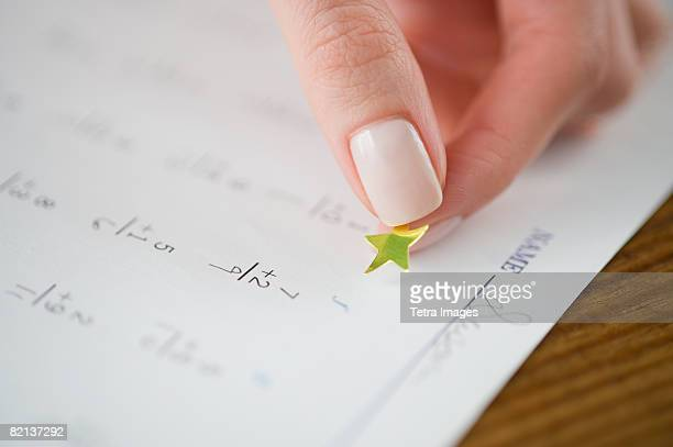 Teacher affixing gold star to math worksheet