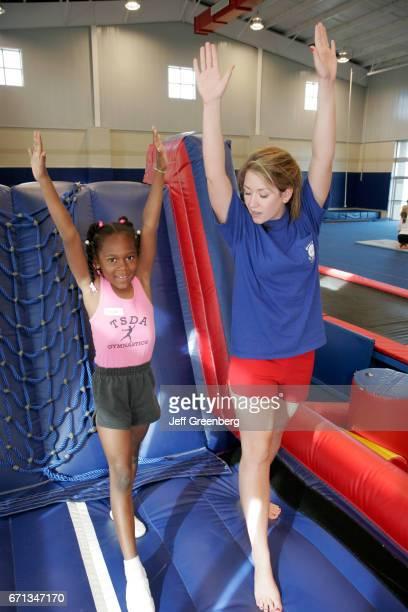 A teacher and a black girl in a gymnastics class at Sportsplex
