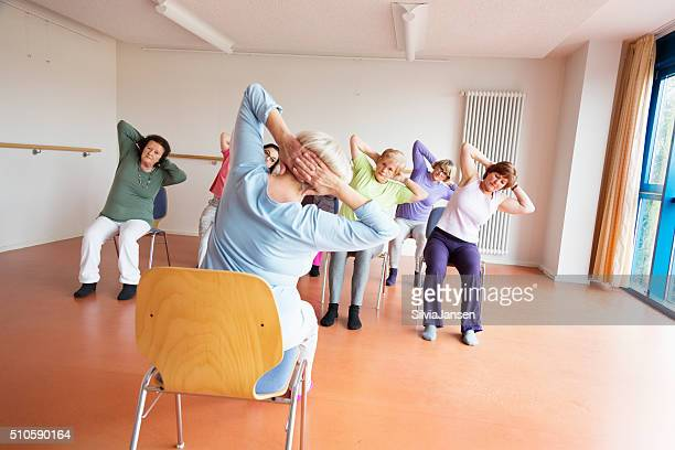 teacher and active senior women yoga class on chairs - chair stock pictures, royalty-free photos & images