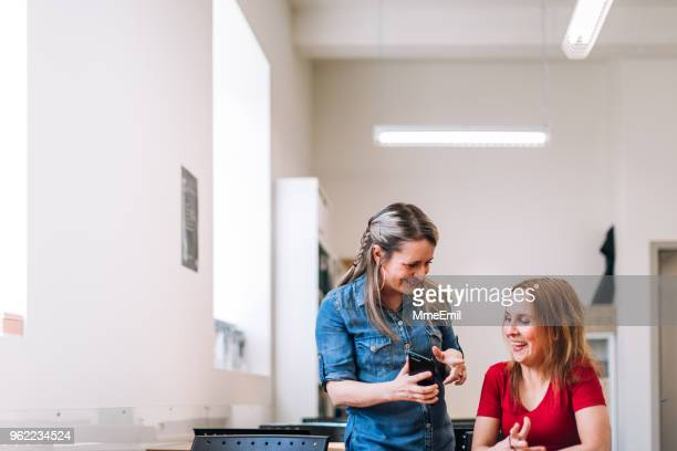a teacher and an adult student looking at a mobile phone and laughing - community centre stock pictures, royalty-free photos & images