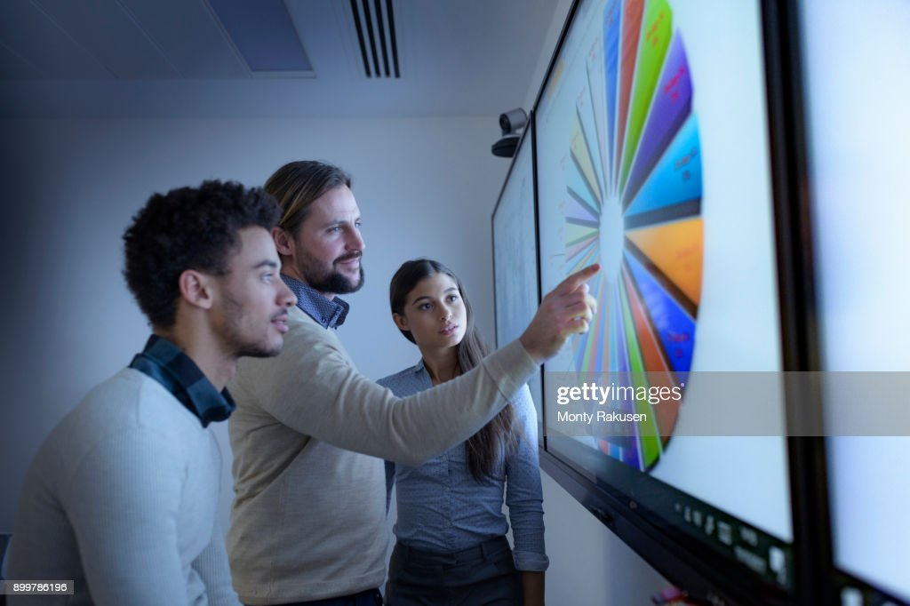 Teacher and apprentices studying graphical screen display in railway engineering facility : Stock Photo