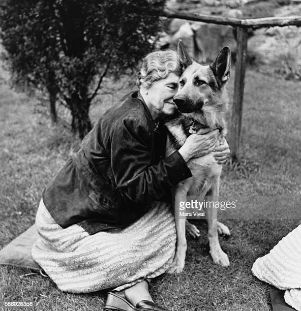 Teacher and author Helen Keller hugs her German shepherd on a garden lawn Keller achieved wide recognition by overcoming blindness and deafness to...