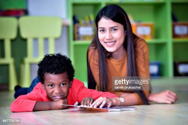 Teacher and boy having fun on learning in an international school  library.