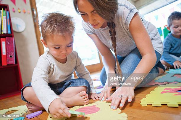 teacher and boy working with puzzle at nursery school - preschool building stock pictures, royalty-free photos & images