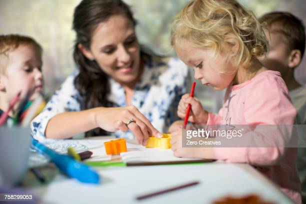 teacher and children drawing - kindergarten stock-fotos und bilder