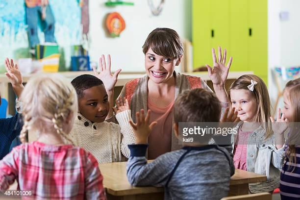 Teacher and children having fun in kindergarten class