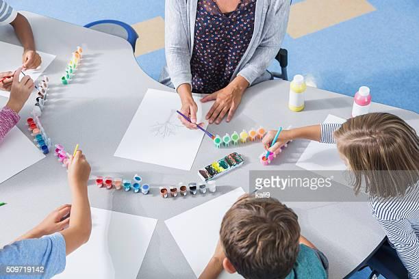 Teacher and children in art class at school