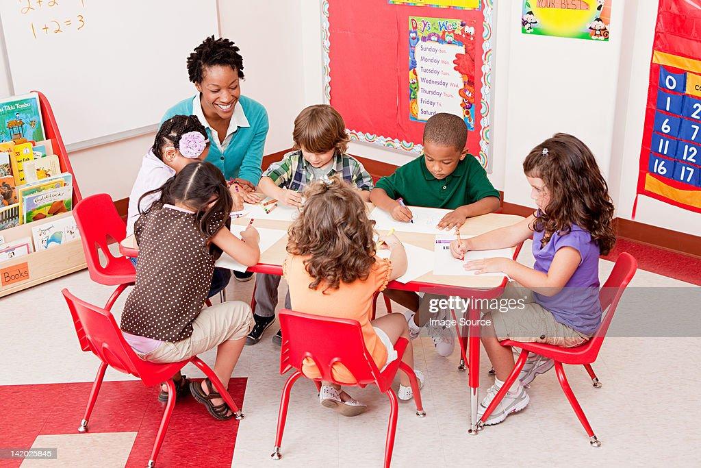 Teacher and children in school art class : Stock Photo