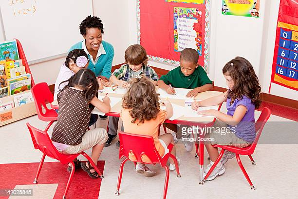 Teacher and children in school art class