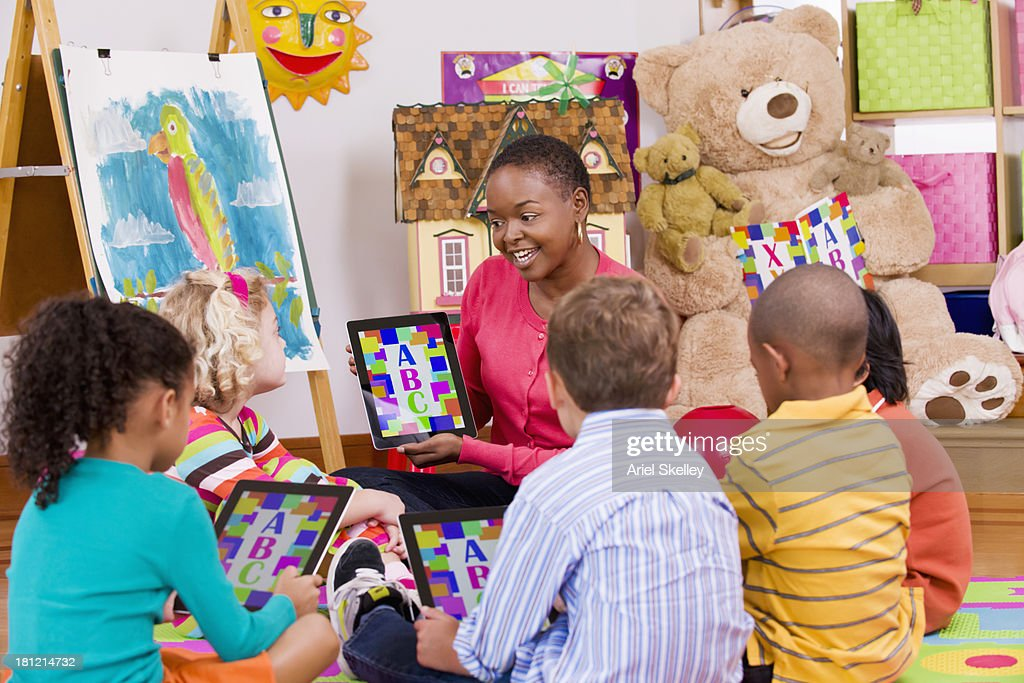 Teacher and children using tablet computers in class : Stock Photo