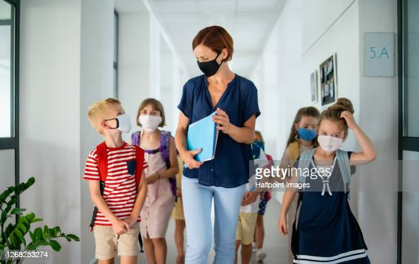 teacher and children with face mask back to school after coronavirus quarantine. - teacher stock pictures, royalty-free photos & images