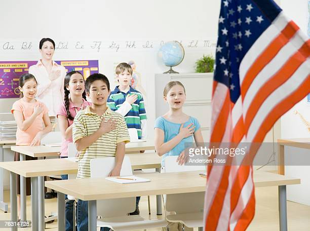 Teacher and five pupils (8-11) saluting American flag in classroom