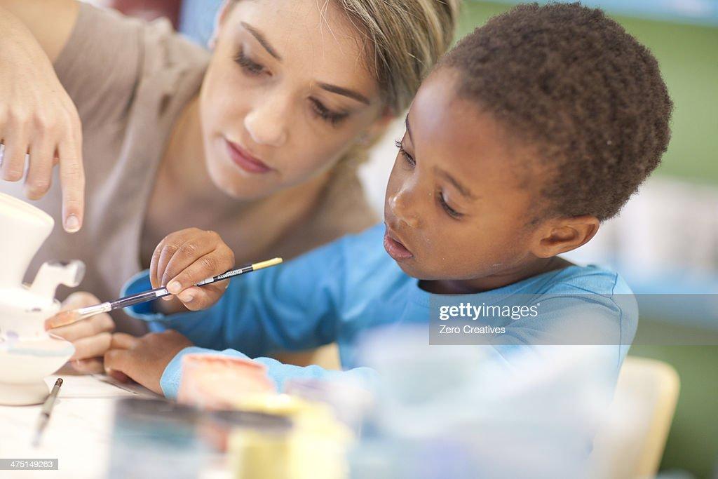 Teacher and girl in art class : Stock Photo