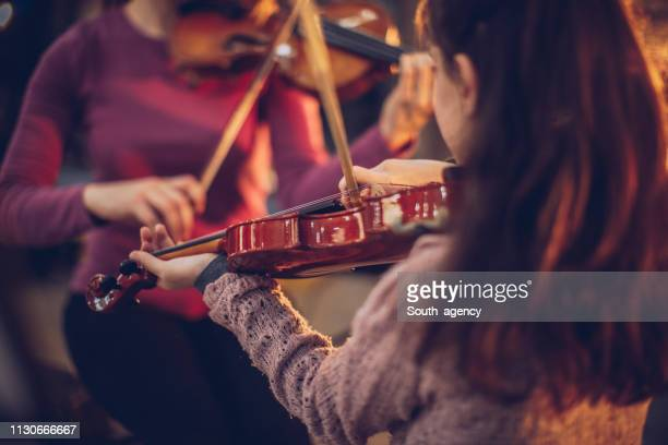 teacher and girl playing violins together - stringed instrument stock pictures, royalty-free photos & images
