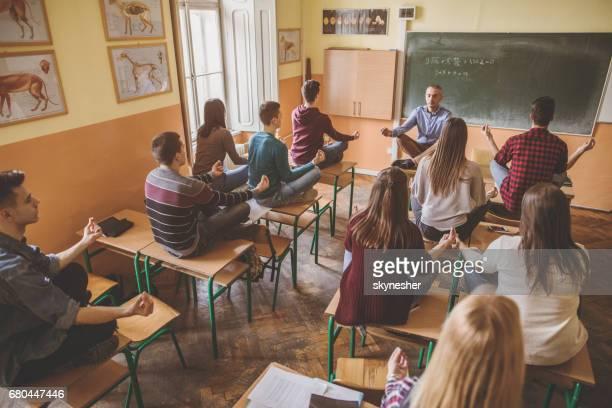 Profesor y grupo de estudiantes practicando Yoga en el aula.