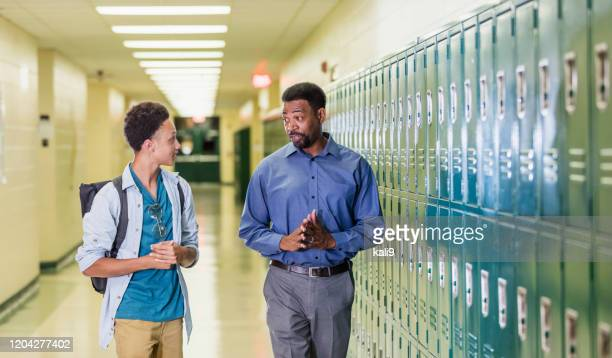 teacher and high school student walking in hallway - school principal stock pictures, royalty-free photos & images