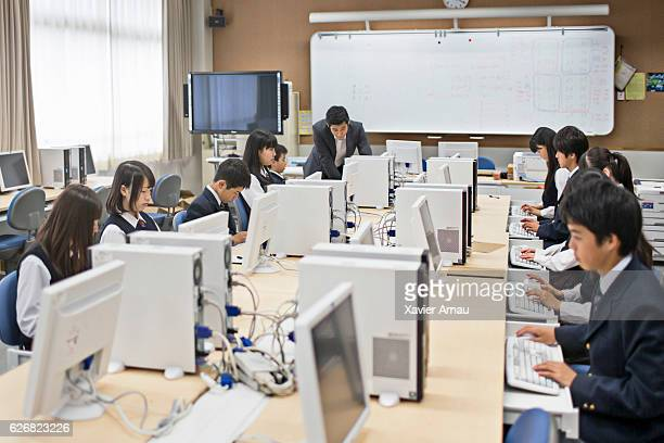 Teacher and high school students using computers