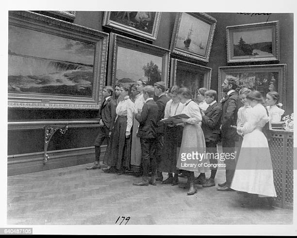 A teacher and his high school class examine painting in an art gallery in Washington D C ca 1900