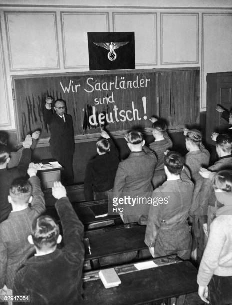 A teacher and his pupils give the Nazi salute shortly after the population of the Saarland voted in a plebiscite to rejoin Germany January 1935 Under...