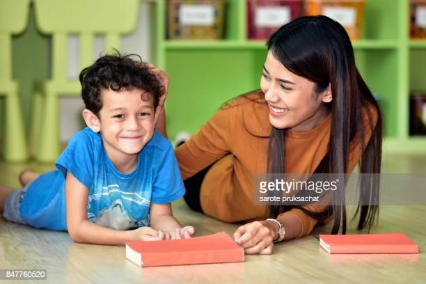 Teacher and kindergarten student having fun on learning in an international school  library.