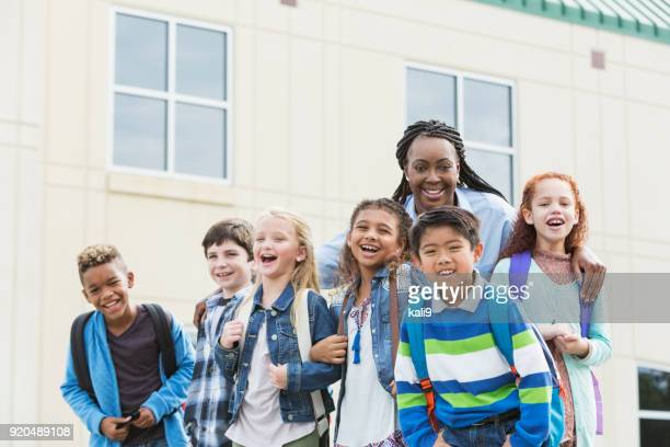 teacher and multi-ethnic children carrying backpacks - school principal stock pictures, royalty-free photos & images