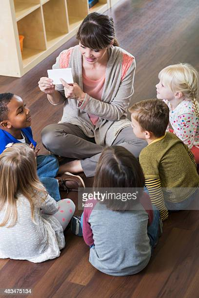 Teacher and preschoolers sitting on floor in circle