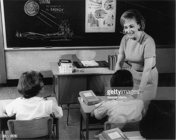 teacher and primary school students in classroom - 20th century stock pictures, royalty-free photos & images