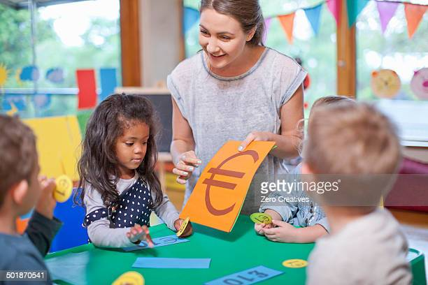 Teacher and pupils counting euro currency at nursery school