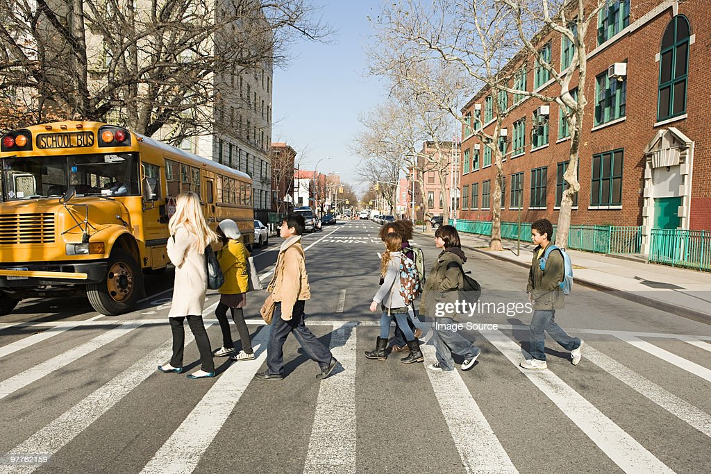Teacher and pupils crossing road : Stock Photo