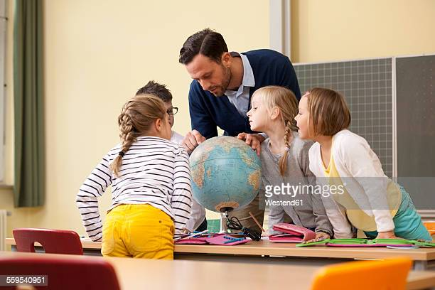 teacher and pupils looking at globe in classroom - teacher bending over stock photos and pictures
