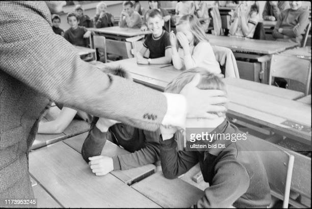Teacher and pupils playing scene of corporal punishment