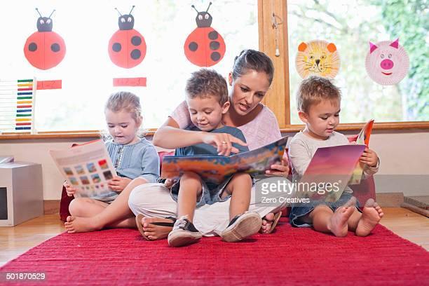 Teacher and pupils reading story books at nursery school