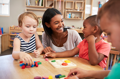 Teacher And Pupils Using Wooden Shapes In Montessori School 684059604