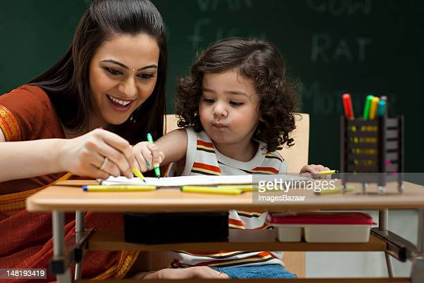 teacher and schoolgirl (2-3) at desk - day stock pictures, royalty-free photos & images