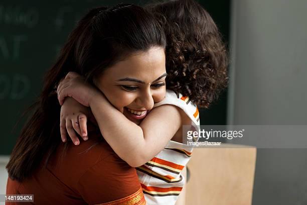 Teacher and schoolgirl (2-3) embracing