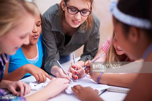teacher and schoolgirls writing on paper - teacher bending over stock photos and pictures