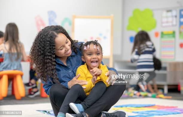 a teacher and smiling pre-school student - fatcamera stock pictures, royalty-free photos & images