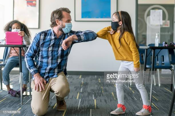 teacher and student greet with elbow bump during covid-19 pandemic - teacher stock pictures, royalty-free photos & images
