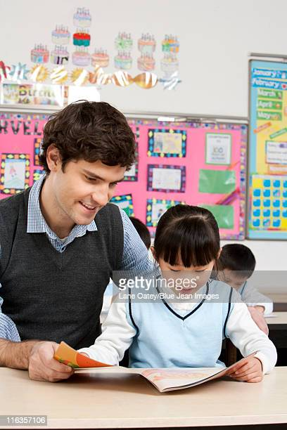 Teacher and student reading together in class