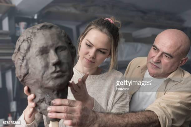 教師と生徒が粘土の顔を彫刻