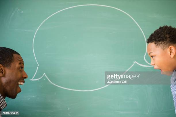 Teacher and student talking by empty speech bubble