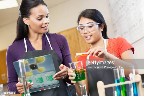 Teacher and student working with chemicals in classroom