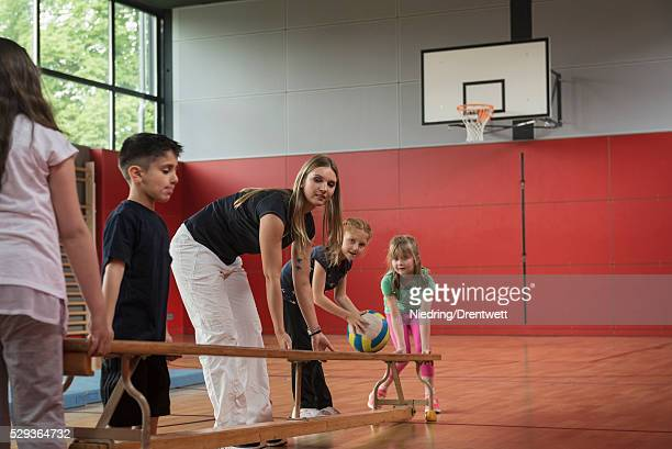 teacher and students carrying bench in sports hall, munich, bavaria, germany - school gymnastics stock photos and pictures