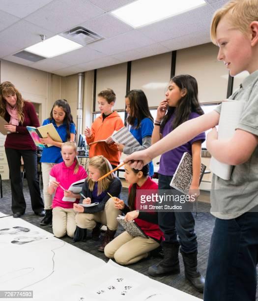 teacher and students examining crime scene in classroom - multiculturalismo foto e immagini stock