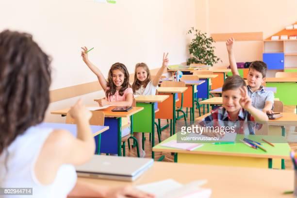 lehrer und schüler im klassenzimmer - kind im grundschulalter stock-fotos und bilder