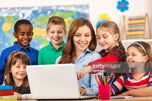 Lehrer und Schüler im Klassenzimmer mit Laptop