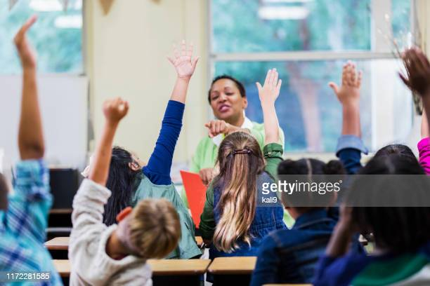 teacher and students in elementary school classroom - arms raised stock pictures, royalty-free photos & images