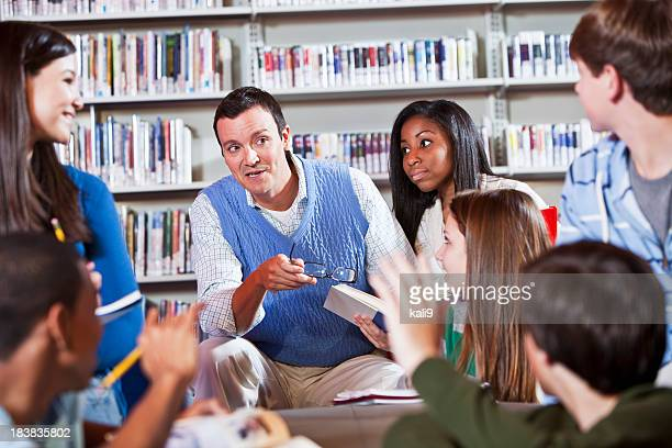 Teacher and students in library discussing books