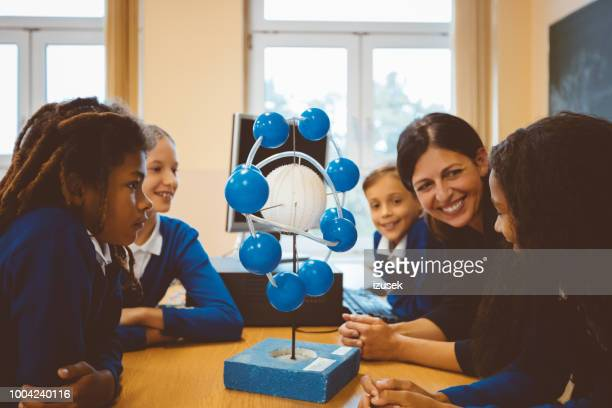 teacher and students in science lesson - physics stock pictures, royalty-free photos & images